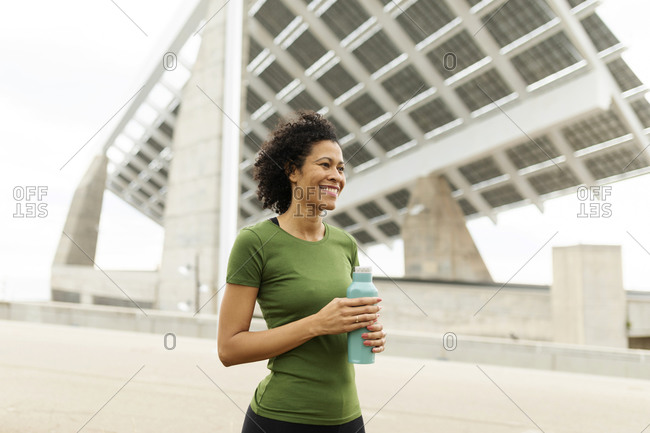 Smiling woman holding water bottle looking away while standing against built structure in city