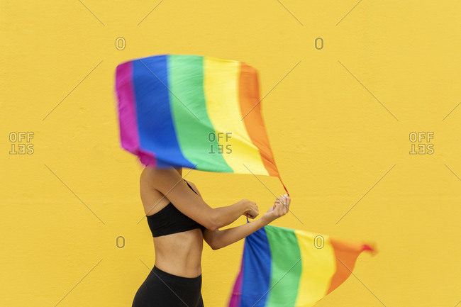 Woman waving rainbow flags while standing against yellow wall in city