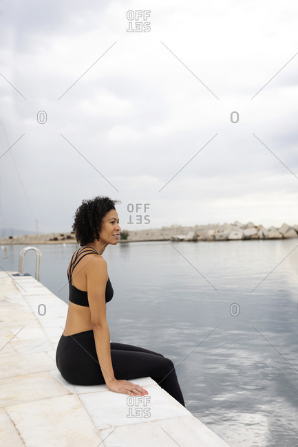 Thoughtful woman with curly hair sitting on promenade by sea against cloudy sky