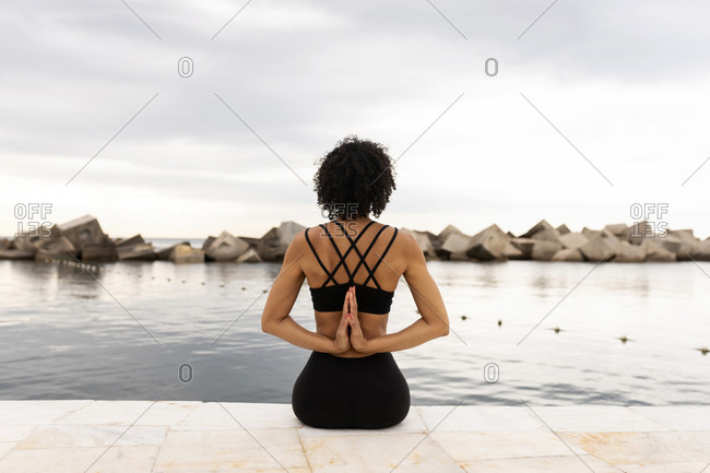 Mid adult woman with curly hair practicing yoga while sitting on promenade by sea