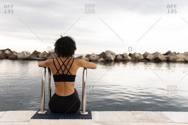 Mid adult woman with curly hair looking at sea while sitting by railings on promenade