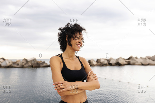 Smiling mid adult woman with arms crossed looking away while standing against sea