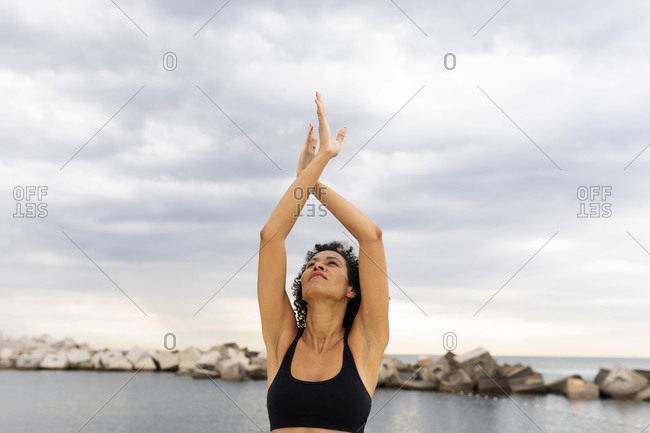Smiling mid adult woman with arms raised exercising against sea and cloudy sky