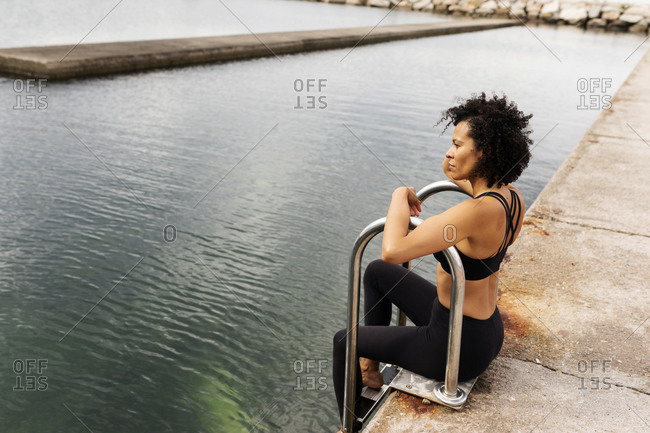 Thoughtful woman looking at sea while sitting on promenade in city