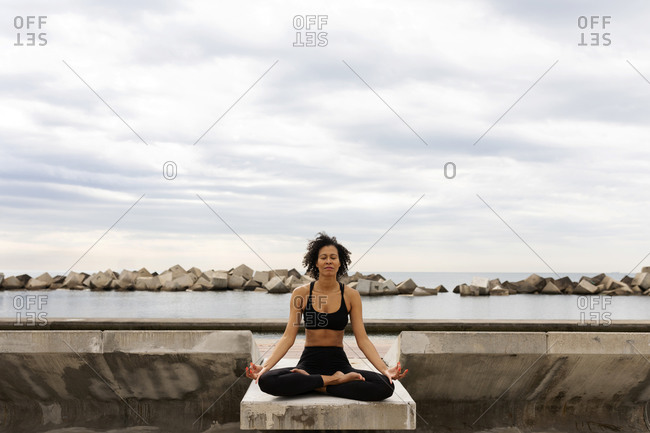 Mid adult woman with eyes closed meditating on promenade against sea