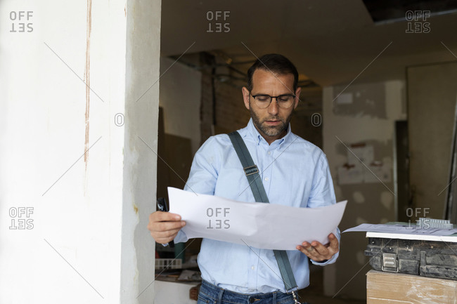 Architect studying plan in a house under construction
