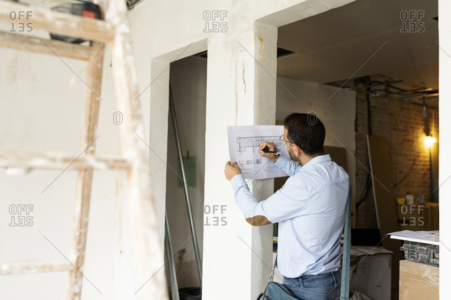 Architect working on plan in a house under construction