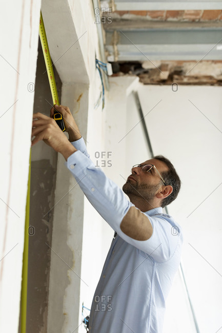 Architect using tape measure in a house under construction