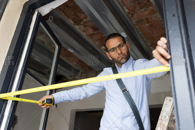 Architect using tape measure on window frame in a house under construction