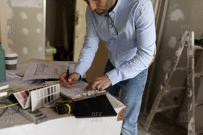 Architect at work with construction plan and color swatch