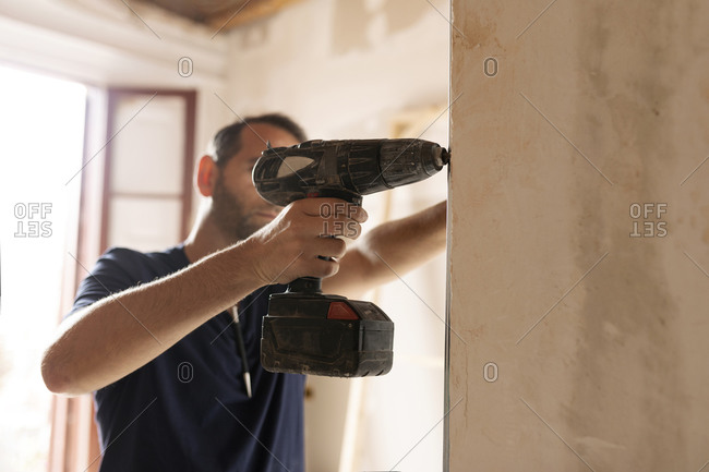 Construction worker using drill at a wall