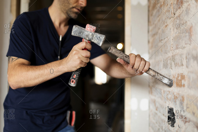 Construction worker using hammer and chisel at a brick wall