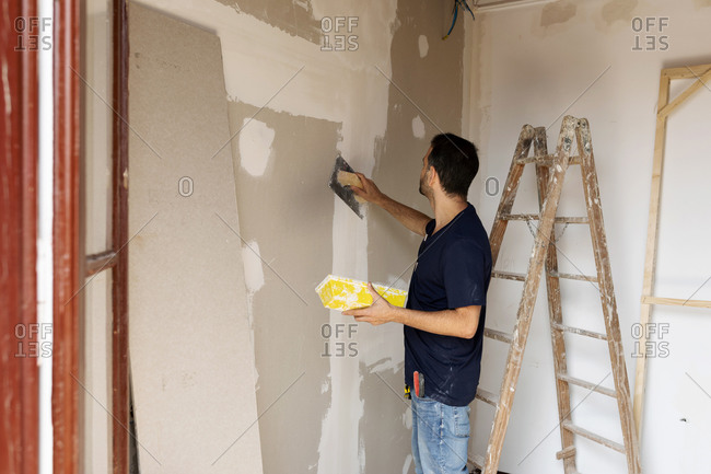 Construction worker plastering wall in a house