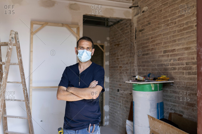 Portrait of a man wearing protective face mask in a house under construction