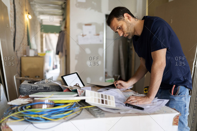 Man working on construction plan and color swatch