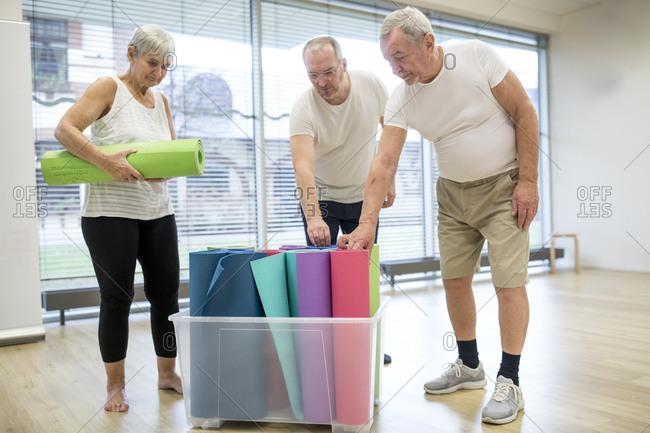 Seniors putting back yoga mats into plastic container in yoga studio