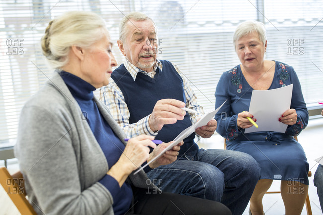 Seniors in therapy group in retirement home writing down notes on sheets of paper