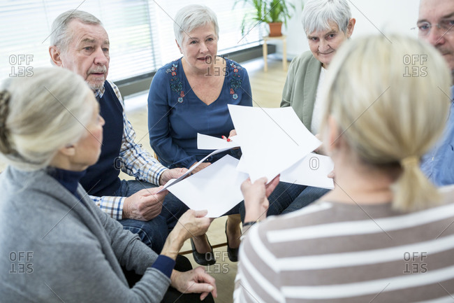 Group of seniors attending therapy group in retirement home- using sheets of paper