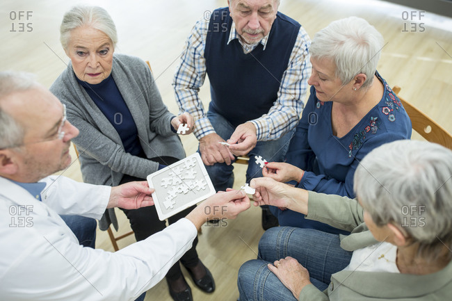 Doctor playing jigsaw puzzle with group of seniors in retirement home