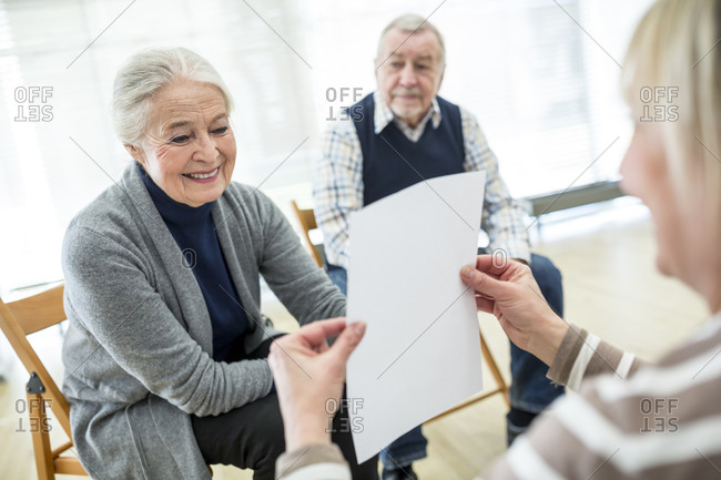 Senior woman in therapy group on retirement home reading sheet of paper