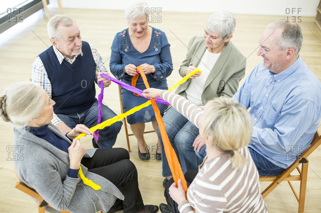 Group of deniors playing with colorful ribbons for building community