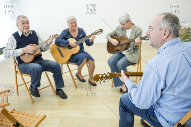 Seniors in retirement home attending guitar class- making music