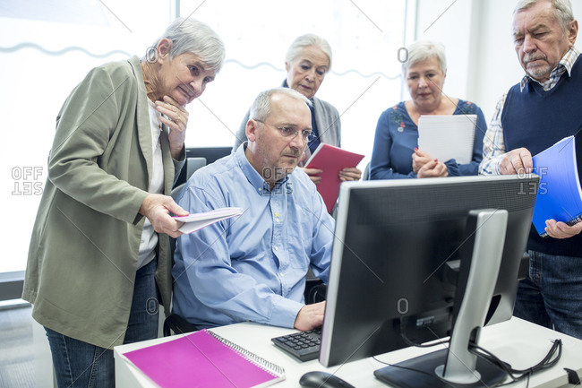 Active seniors attending computer course- watching instructor and taking notes