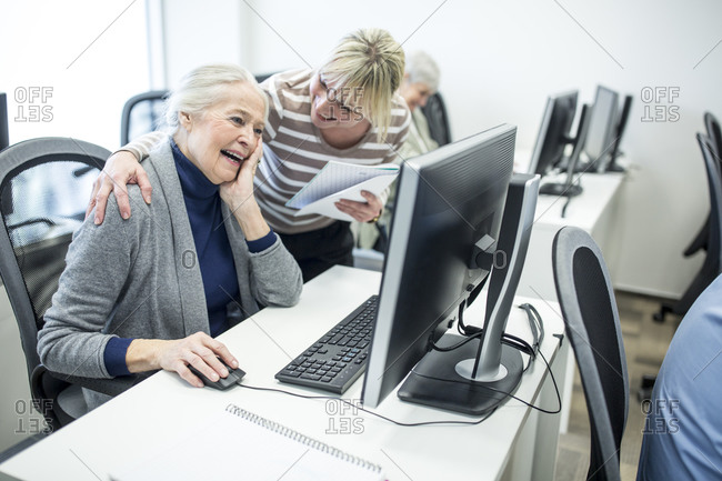 Active seniors attending computer course- instructor giving advice