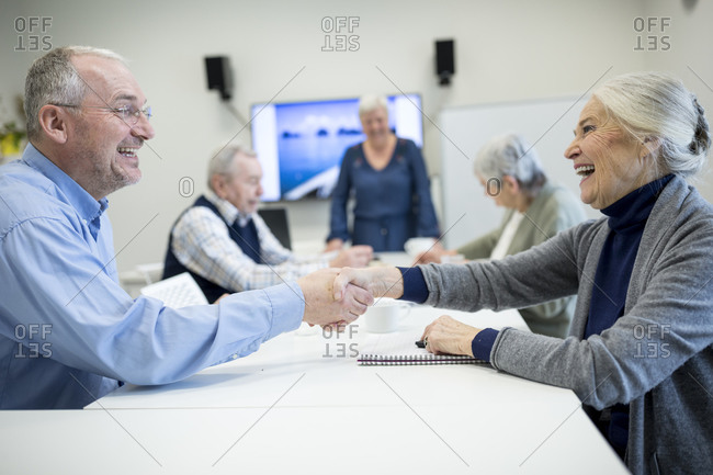 Senior citizens meeting at skill enhancement course- shaking hands