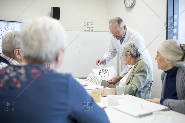Doctor explaining brain functions to group of senior citizens