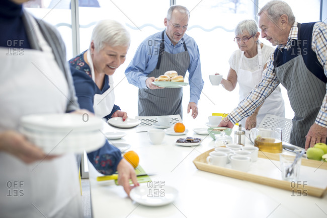 Group of seniors laying table for coffee party in retirement home
