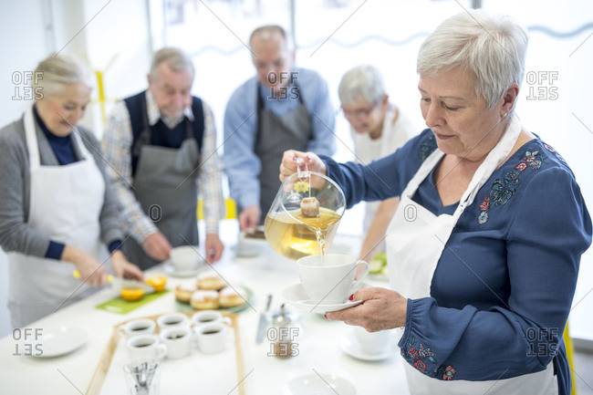 Senior woman pouring tea in cup for coffee party in retirement home