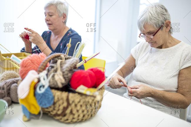 Senior women knitting together in needlework group of retirement home