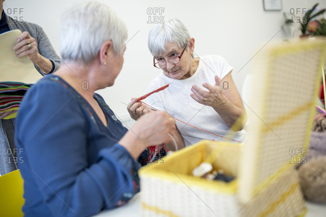 Two senior women in retirement home talking while knitting in needlework group