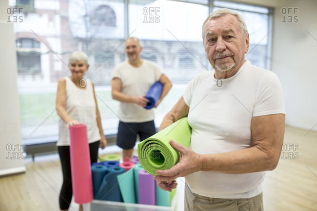 Happy senior man holding yoga mat after class