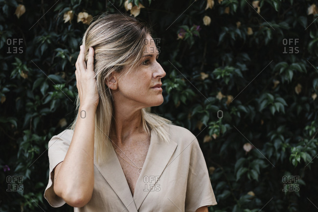 Close-up of thoughtful woman with hand in hair against plants