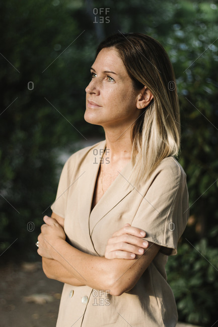 Close-up of thoughtful woman with arms crossed standing in park