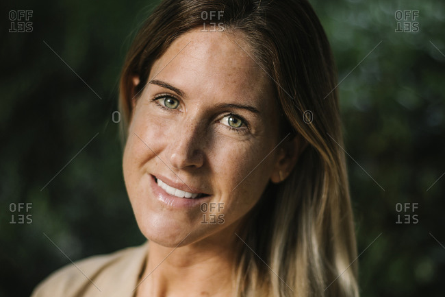 Close-up of smiling mid adult woman with hazel eyes in park