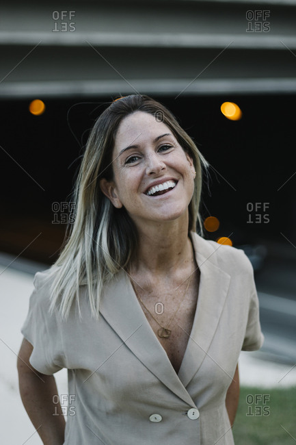 Close-up of happy mid adult woman laughing while standing outdoors
