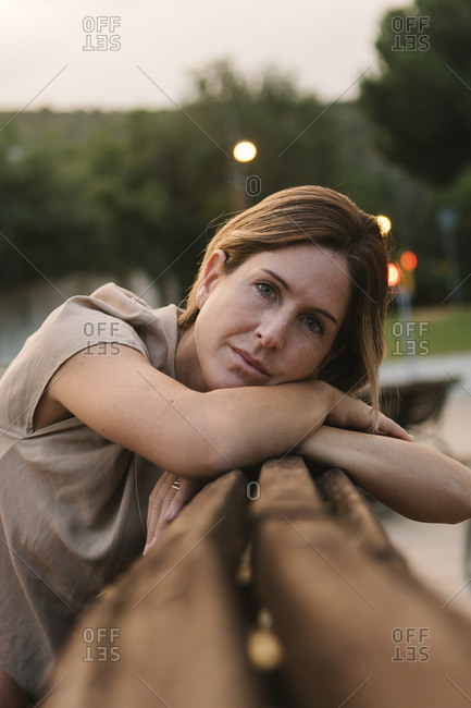 Close-up of thoughtful mid adult woman leaning on railing in park at sunset