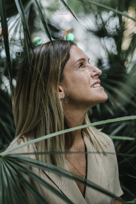 Close-up of smiling mid adult woman contemplating amidst plants in park