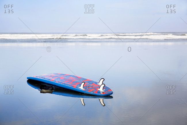 Surf board reflected in tidal water at Cox Beach, Tofino, British Columbia, Canada