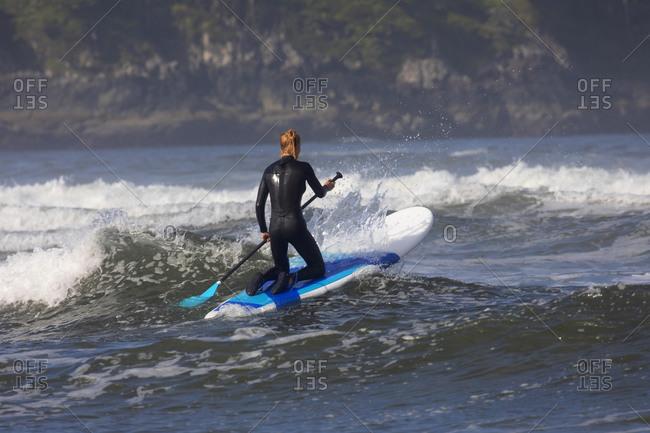 Female paddle boarding out to sea near Cox Beach, Tofino, British Columbia, Canada