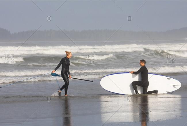 Tofino, British Columbia, Canada - August 6, 2020: Couple paddle boarding in surf at Cox Beach, Tofino, British Columbia, Canada