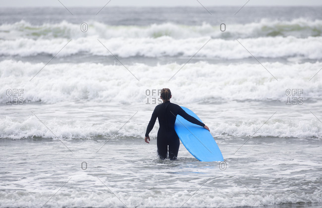 Female surfer waiting for the surf, Cox Beach, Tofino, British Columbia, Canada