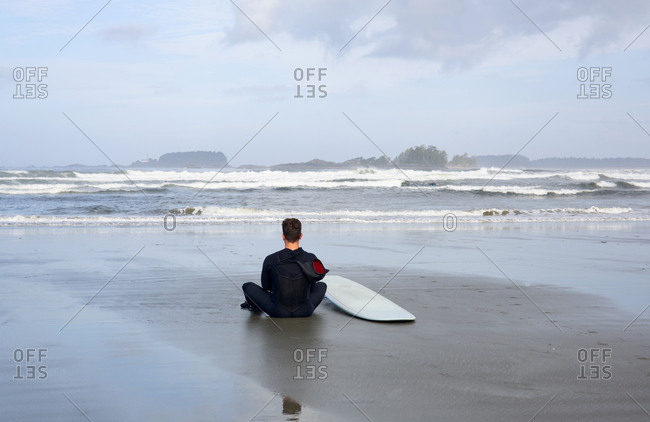 Man sitting on Cox Beach waiting for the surf, Tofino, British Columbia, Canada