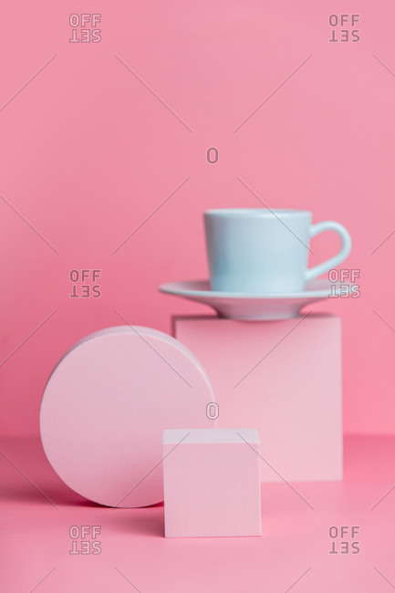 Geometric shapes and a white coffee cup on pink background