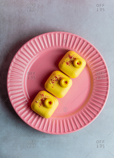 Three yellow raw desserts without gluten, sugar and flour on a plate