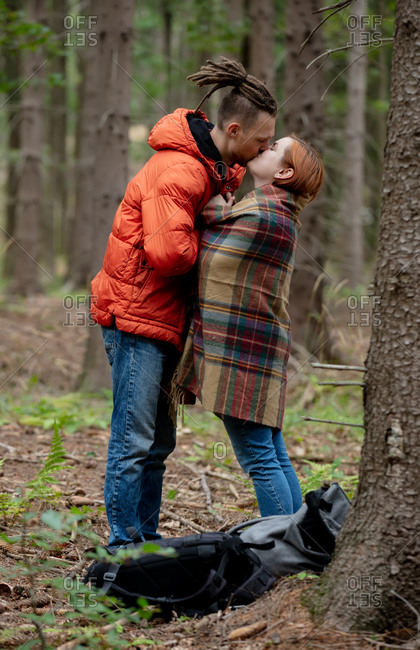 Young couple kissing among the pines in an autumn forest in Poland