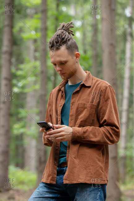 Young man with a mobile phone is looking for direction in the forest